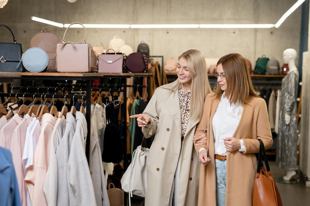 Happy young blond woman in elegant beige coat pointing at new seasonal collection in boutique while showing one of items to her mother