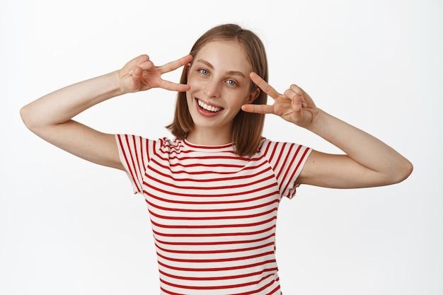 平和のvサイン、目の近くのディスコの指を示し、白い完璧な笑顔で笑って、正面を見て、白い壁に立って幸せな若いブロンドの女性