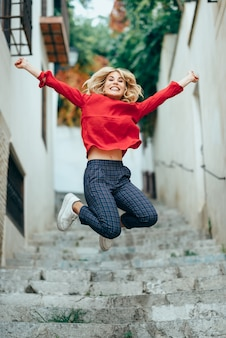 Happy young blond woman standing on beautiful steps in the street.
