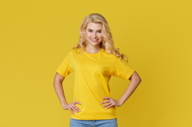 Happy young blond woman standing over yellow wall