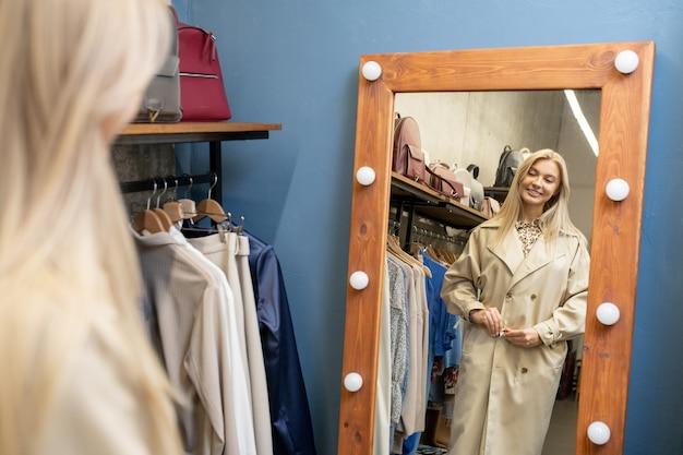 Счастливая молодая блондинка примеряет новое элегантное бежевое пальто перед зеркалом в раздевалке, выбирая новую одежду на весну