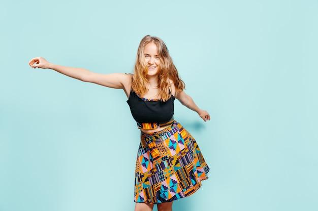 Счастливая молодая блондинка танцует и смотрит в камеру в красочном платье на синем фоне