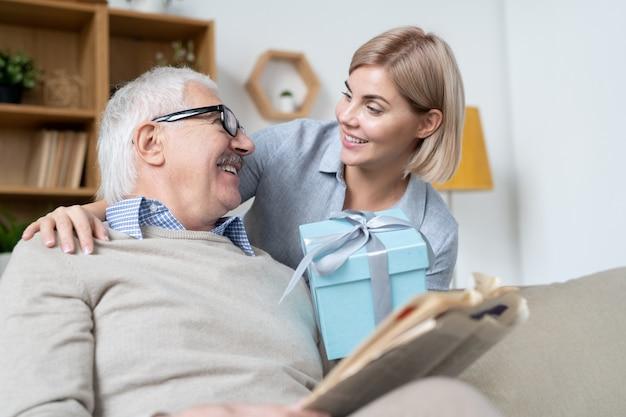 Счастливая молодая блондинка дарит своему зрелому отцу синюю подарочную коробку с подарком на день рождения или рождество, глядя на него