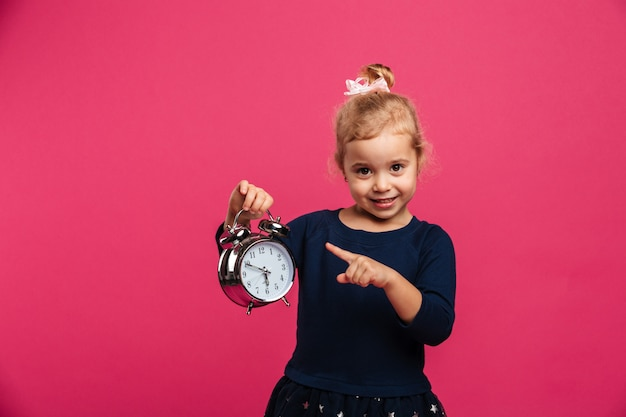Happy young blonde girl holding alarm clock and pointing on it while looking at the camera over pink wall