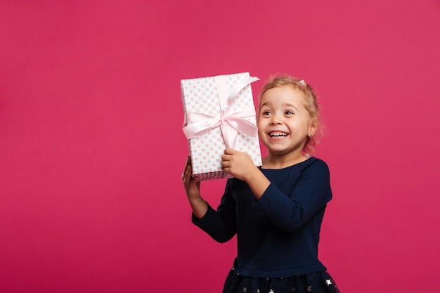 Happy young blonde girl holding gift box and rejoices