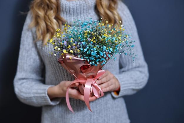 Счастливая молодая блондинка в светло-сером свитере держит в руках букет цветов на темно-сером монохромном фоне.