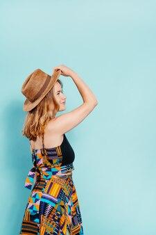 Счастливая молодая блондинка боком в очень красочном платье держит соломенную шляпу на синем фоне