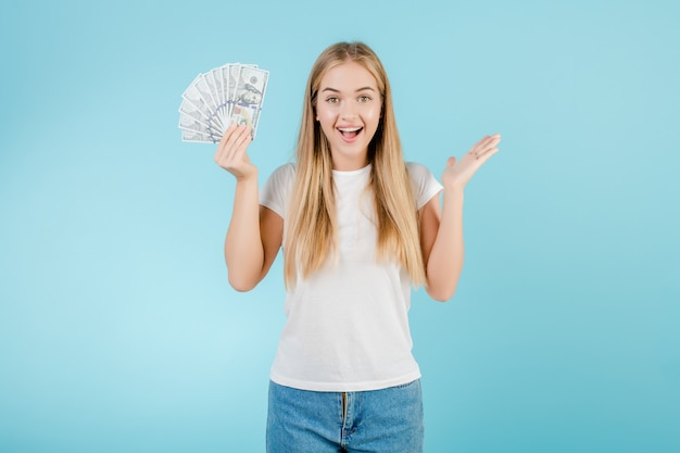 Happy young blonde girl with dollar money in her hand isolated over blue