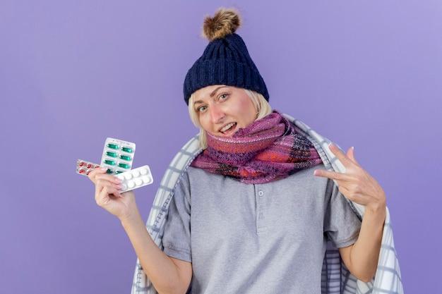 겨울 모자와 스카프를 착용하는 행복 한 젊은 금발의 아픈 슬라브 여자