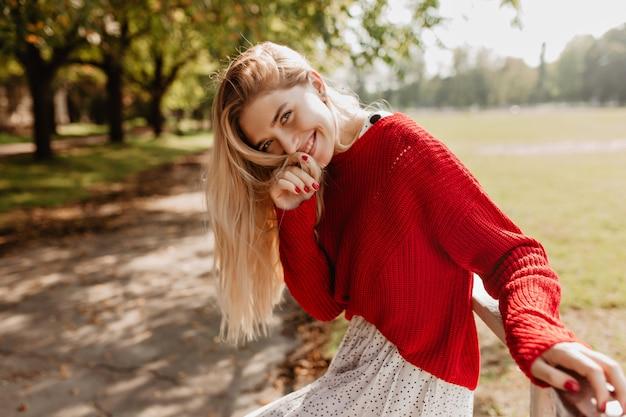 トレンディな赤いセーターと秋の公園で笑顔の白いスカートで幸せな若いブロンド。屋外でポーズをとるナチュラルメイクのスタイリッシュな女の子。