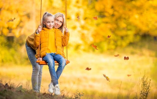 ゆるい髪の幸せな若いブロンドのお母さんは、公園で秋のロープスイングのブランコで娘を振る。