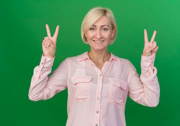 녹색 배경에 고립 된 평화 표지판을 하 고 행복 한 젊은 금발 슬라브 여자