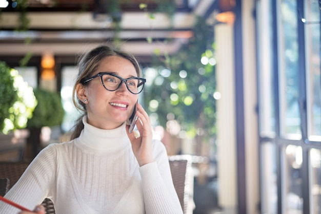 Happy young blonde woman in glasses working in a restaurant