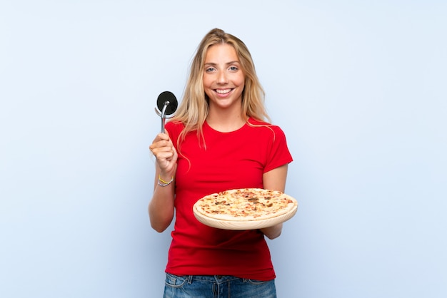 Happy young blonde woman holding a pizza over isolated blue wall