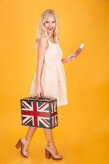 Happy young blonde woman holding uk printed suitcase