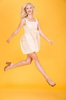 Счастливая молодая белокурая скача изолированная женщина