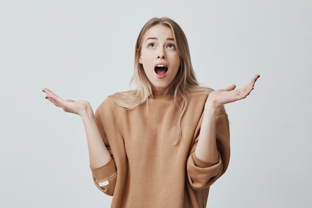 Happy young blonde woman looking upwards in amazement with opened mouth, clapping hands in full disbelief isolated against grey wall. positive emotions, facial expressions, body language.