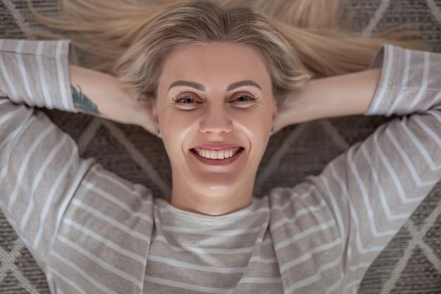 카펫 평면도에 누워 행복 한 젊은 금발의 여자