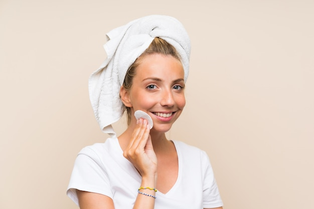 Happy young blonde woman removing makeup from her face with cotton pad