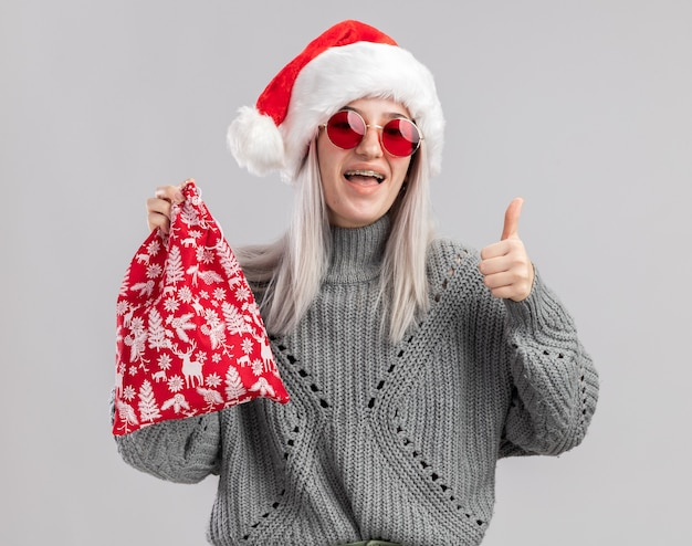 Happy young blonde woman in winter sweater and santa hat holding santa red bag with christmas gifts  smiling cheerfully showing thumbs up  standing over white wall