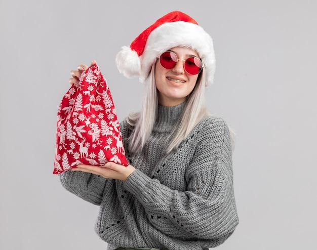 Felice giovane donna bionda in maglione invernale e cappello da babbo natale che tiene in mano una borsa rossa con regali di natale che sorride allegramente in piedi sul muro bianco white