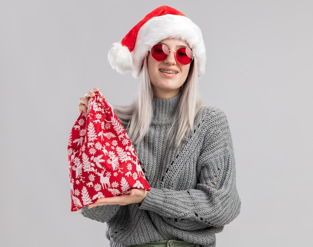 Happy young blonde woman in winter sweater and santa hat holding santa red bag with christmas gifts  smiling cheerfully standing over white wall