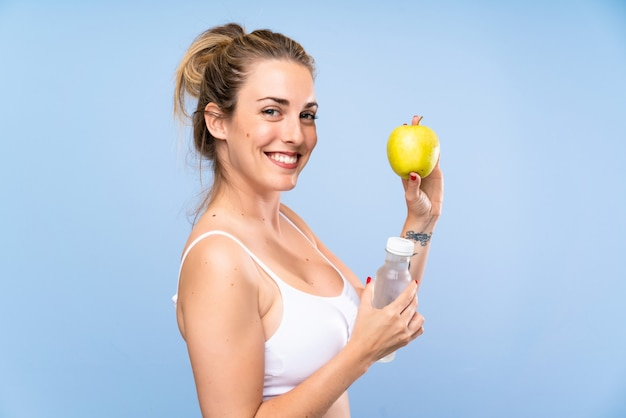 Happy young blonde woman with an apple and a bottle of water
