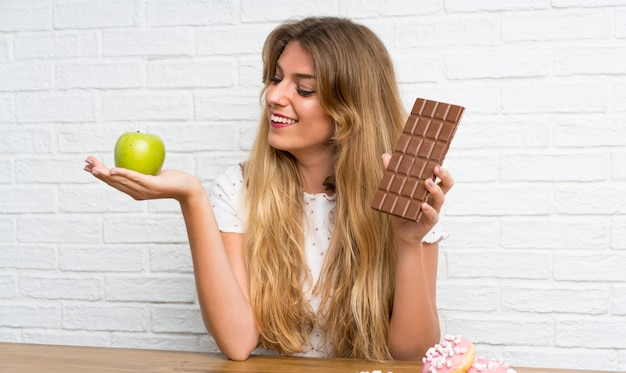Happy young blonde woman with chocolat and an apple