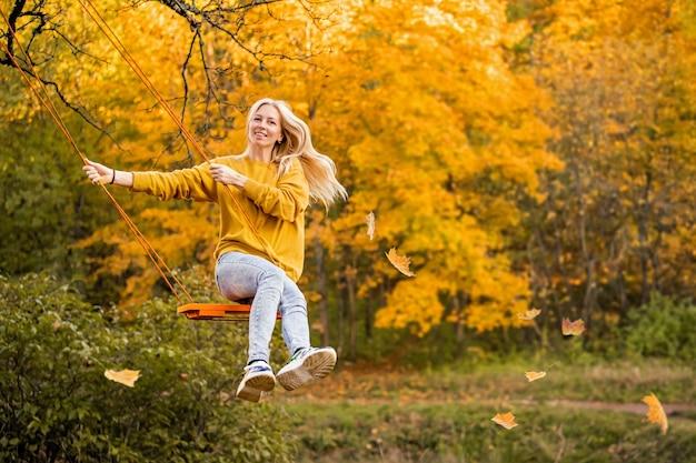 ゆるい髪の幸せな若いブロンドの女性は、公園で秋のロープスイングに微笑んで乗ります。