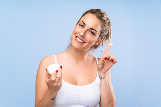 Happy young blonde woman with moisturizer over isolated blue wall