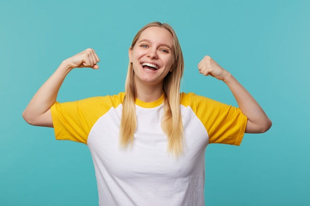 Счастливая молодая голубоглазая длинноволосая блондинка весело смотрит в камеру с широкой улыбкой, показывая сильные бицепсы, стоя на синем фоне