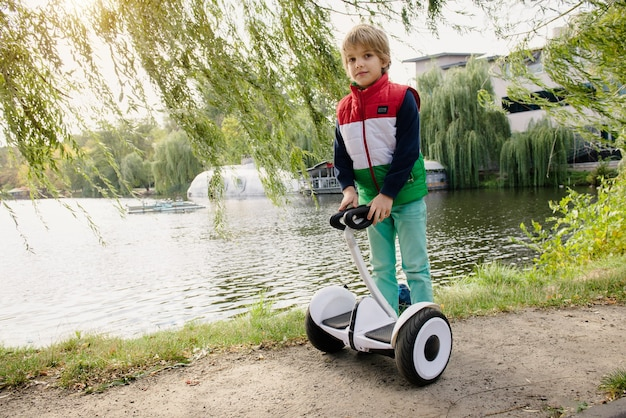 日当たりの良い秋の公園で電気ホバーボードでバランスをとる幸せな少年