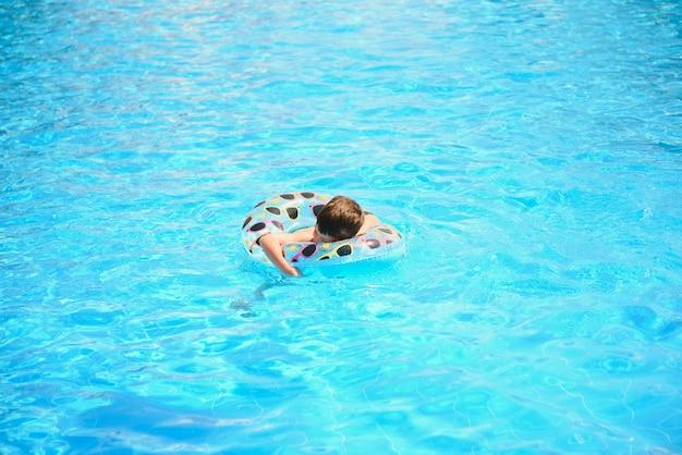 Счастливый молодой мальчик, плавающий в бассейне на надувном кольце