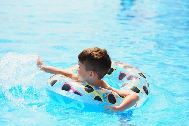 Счастливый мальчик плавает в бассейне с надувным кольцом Premium Фотографии