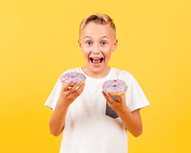 Happy young boy holding doughnuts