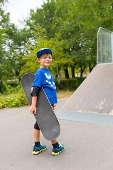 トレンディな青い服を着た幸せな少年がスケートパークで新しいスケートボードを持ってカメラに笑顔を与えます