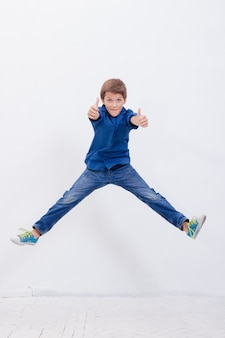 Happy young boy jumping  on white background