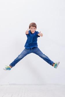 Felice giovane ragazzo che salta su sfondo bianco