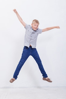 Happy young boy jumping over a white background