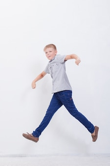 Happy young boy jumping  on white