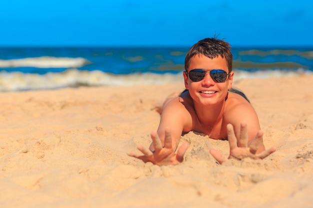 Счастливый молодой мальчик на берегу моря