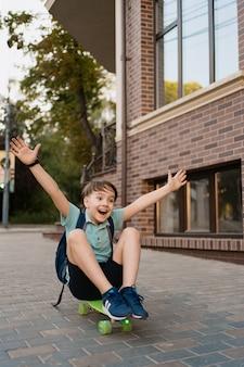 市内のスケートボード、ペニーボードに乗って白人の子供で遊んで幸せな少年
