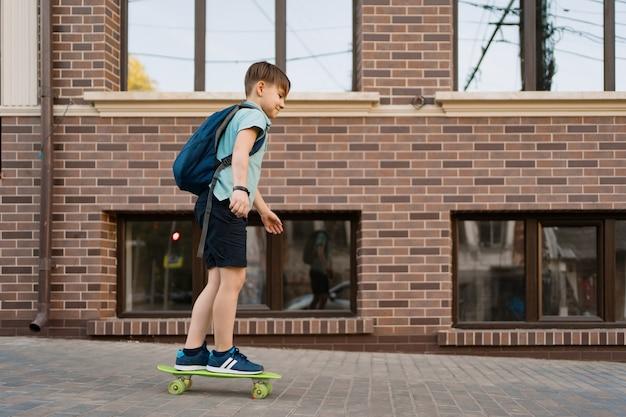 Giovane ragazzo felice che gioca su skateboard in città, bambino caucasico cavalcando penny board