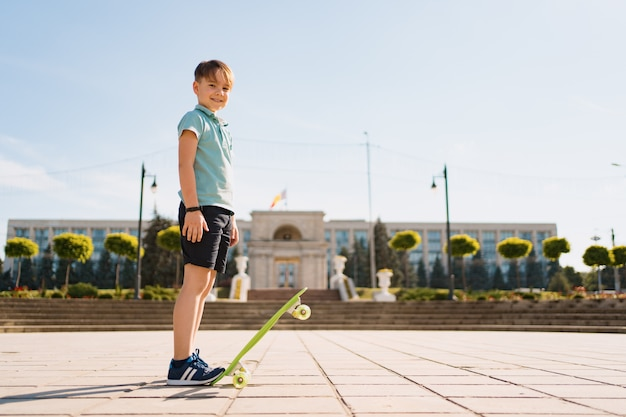 Felice ragazzo giocando su skateboard nel parco, bambino caucasico cavalcando penny board, praticare skateboard.