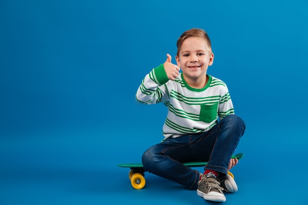 Happy young boy sitting on skateboard and showing thumb up