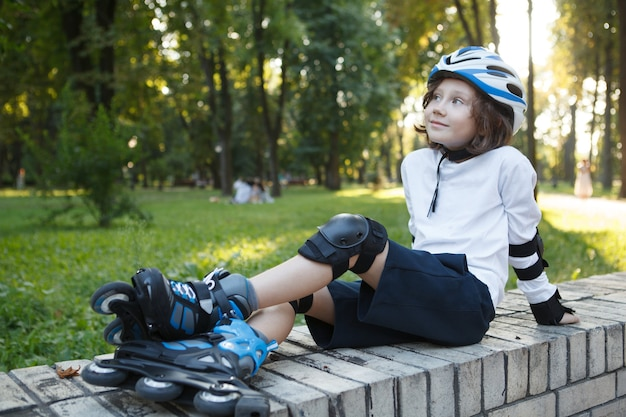 Happy young boy wearing rollerskates and helmet, resting at the park after skating