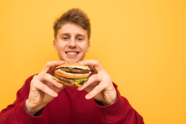 Счастливый молодой мальчик с бургером в руках стоит на желтом