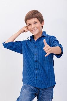 Счастливый молодой мальчик с жестом вызова на белом фоне