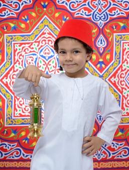 Счастливый мальчик с фесом и фонарем празднует рамадан