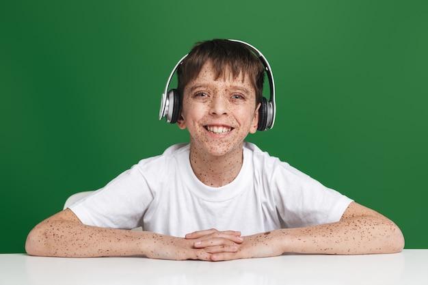 緑の壁の上のテーブルのそばに座っている間、正面を見てヘッドフォンでそばかすのある幸せな少年